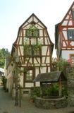 Bauholzrahmenhaus und -brunnen Stockbild