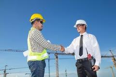 Bauingenieur mit der Arbeitskraft, die Hände am Bau rüttelt Lizenzfreie Stockfotos