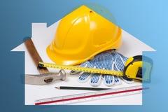 Baukonzept - Arbeitswerkzeuge des Erbauers im blauen Haus Lizenzfreie Stockbilder