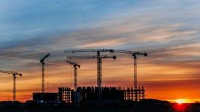 Baukräne, die bei Sonnenuntergang, Arbeitskräfte teilgenommen an Bau, Zeitspanne arbeiten stock video