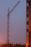 Baukran auf dem Standort, unfertiges Haus, Nebel bedeckt die obersten Stockwerke und glättet Dämmerung Lizenzfreie Stockfotografie