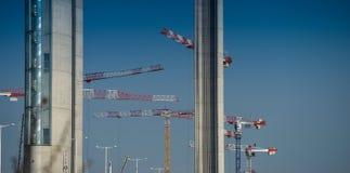 Baukräne und -standort gegen einen blauen Himmel Stockbilder