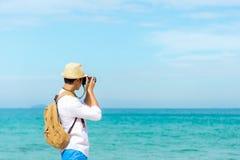 Baum auf dem Gebiet Glücklicher lächelnder kaukasischer touristischer asiatischer junger Mann, der Kamera hält lizenzfreie stockbilder