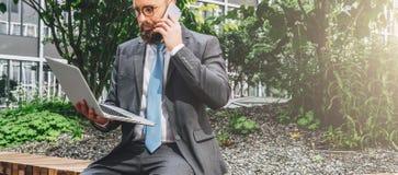 Baum auf dem Gebiet Junger bärtiger Geschäftsmann im Anzug und Bindung, die im Park auf Bank sitzt, Laptop hält und am Handy spri stockfotografie