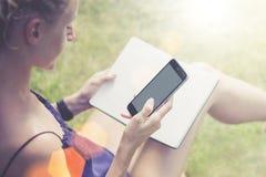Baum auf dem Gebiet Nahaufnahme von Smartphone in der Hand der jungen Frau, die im Park auf Rasen- und Lesebuch sitzt Mädchenfunk Stockfotografie
