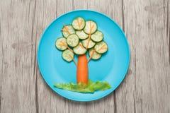 Baum gemacht von der Gurke und von der Karotte auf Platte und Tabelle Lizenzfreie Stockfotos