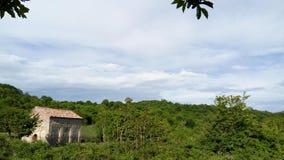 Baum-Himmelblauwolken der Kirche grüne stockbild