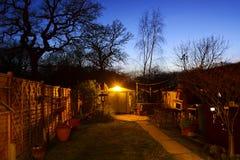 Baum-Schattenbild und Dämmerungs-Garten Lizenzfreies Stockbild