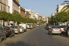 Baum zeichnete schmale Straße des Dorfs in Süd-Spanien weg von der Landstraße A49 westlich von Sevilla stockbilder