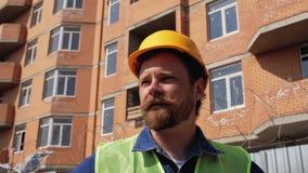 Baumanager in einem gelben Sturzhelm mit einem Bart und einem Schnurrbart spricht gegen die Baustelle 4 K stock video