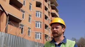 Baumanager in einem gelben Sturzhelm mit einem Bart und einem Schnurrbart spricht gegen die Baustelle 4 K stock footage
