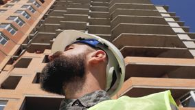 Baumanager in einem Sturzhelm mit einem Bart und Schnurrbart auf dem Hintergrund eines hohen Gebäudes 4K stock footage