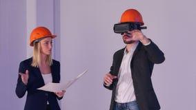 Baumann und weibliche Ingenieure in den Sturzhelmen mit VR-Schutzbrillen Bauvorhaben in 3d handhabend stock footage