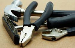 Baumaterialien und Handwerkzeuge auf hölzernem Brett Stockfotos