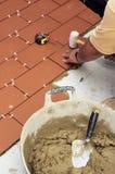Baumaurer, der die Pflasterung des Hofes eines Hauses erneuert Lizenzfreies Stockbild