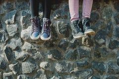 Baumelnde Baby ` s Füße in den Schuhen lizenzfreies stockbild