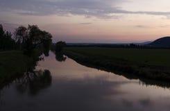 Baumreflexion im Fluss während des Sonnenuntergangs Lizenzfreies Stockbild