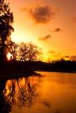 Baumreflexion im See mit drastischem Himmel Lizenzfreie Stockfotografie