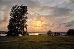 Baumschattenbilder in dem Fluss bei Sonnenuntergang Lizenzfreie Stockfotografie