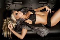 Baumuster gekleidet im Pelz, der auf Sofa legt Stockfoto