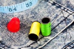 Baumwolle, Nadel und eine Muffe auf Denimjeans Stockfotografie