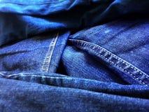 Baumwollstoff- oder Denimeinzelteile von Kleidung warfen im Haufen Stockfotos