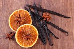 Baunilha perfumada, anis de estrela e laranja secada na prancha de superfície de madeira Imagens de Stock