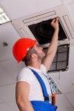 Bauschlosser überprüft Belüftung in der Decke stockfotografie