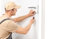 Bauschlosser, der einen Verschluss auf eine Tür installiert Lizenzfreie Stockfotografie