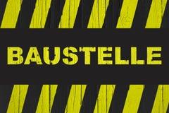 Baustelle auf Deutsch, Warnzeichen der Baustelle mit den gelben und schwarzen Streifen Stockbild