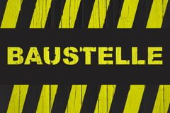 Baustelle in German, construction site warning sign with yellow and black stripes Stock Image
