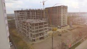Baustelle - Konstruieren des neuen Buldings, der Arbeitskräfte, der Kräne und der Traktoren stock footage