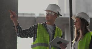 Baustelle Team oder Architekt und Erbauer oder Arbeitskraft mit Sturzhelmen auf einem Gestellbauplan sich besprechen oder stock video footage