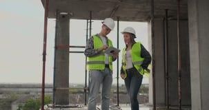 Baustelle Team oder Architekt und Erbauer oder Arbeitskraft mit Sturzhelmen auf einem Gestellbauplan sich besprechen oder stock video