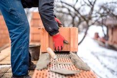 Baustelle und Maurermaurer, der mit Ziegelsteinen, Zement und Mörser für errichtendes Haus arbeitet Stockbilder