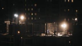 Baustelle-Wohngebäude, schweißende Arbeitskräfte konstruieren an Winternachtdem schneien stock video footage