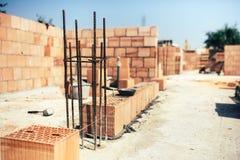 Baustelle, Ziegelsteine auf Zement beim Errichten von Außenwänden setzend, Industrie Lizenzfreies Stockfoto