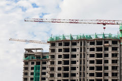 Baustelleansicht des Kranes, des Aufzugs, des Metallstrahls, des Ziegelsteines, der Metallleiter und des Betons Stockfoto