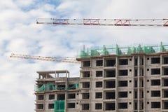 Baustelleansicht des Kranes, des Aufzugs, des Metallstrahls, des Ziegelsteines, der Metallleiter und des Betons Stockbild