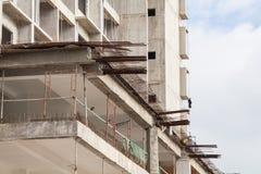 Baustelleansicht des Kranes, des Aufzugs, des Metallstrahls, des Ziegelsteines, der Metallleiter und des Betons Stockfotografie