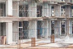 Baustelleansicht des Kranes, des Aufzugs, des Metallstrahls, des Ziegelsteines, der Metallleiter und des Betons Stockfotos