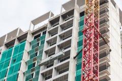 Baustelleansicht des Kranes, des Aufzugs, des Metallstrahls, des Ziegelsteines, der Metallleiter und des Betons Lizenzfreies Stockfoto