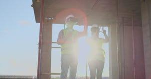Baustelleteam oder Architekt und Erbauer oder Arbeitskraft mit Sturzhelmen auf einem Gestellbauplan sich besprechen oder stock video footage