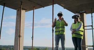 Baustelleteam oder Architekt und Erbauer oder Arbeitskraft mit Sturzhelmen auf einem Gestellbauplan sich besprechen oder stock video