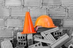 Bausturzhelmsicherheit und -kegel in der Baustelle Stockbilder