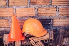 Bausturzhelmsicherheit und -kegel in der Baustelle Lizenzfreie Stockfotografie