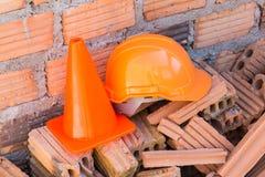 Bausturzhelmsicherheit und -kegel in der Baustelle Lizenzfreies Stockfoto