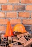 Bausturzhelmsicherheit und -kegel in der Baustelle Lizenzfreies Stockbild