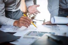 Bautechnik oder -architekt einen Plan bei der Pr?fung von Informationen ?ber das Zeichnen und das Skizzieren besprechen, treffend stockfoto