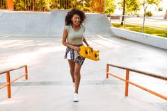 Bautiful african cheerful woman with skateboard. Stock Photos